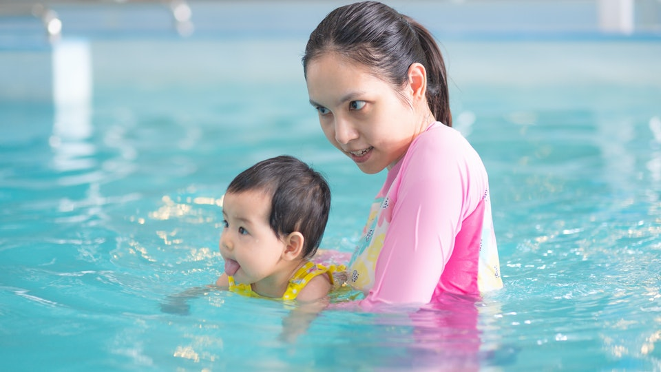 Mother and asian baby girl swimming in a pool, early development class for infants swimming. Baby swimming concept.
