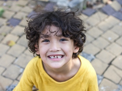 Curly hair mixed kid with natural loose tooth with toned color and lighting and selective focus