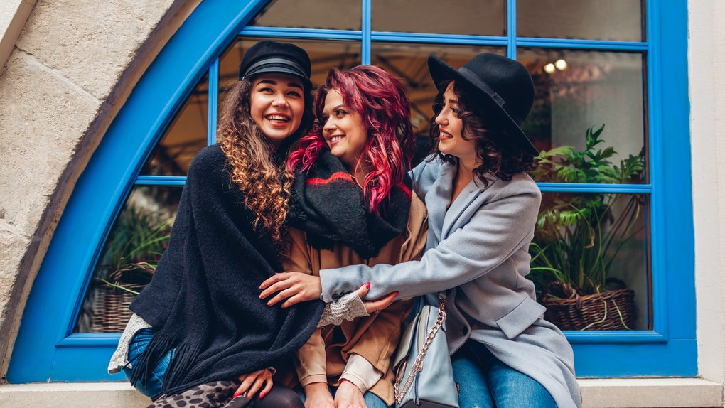 Young women hugging and laughing on city street. Best friends having good time together