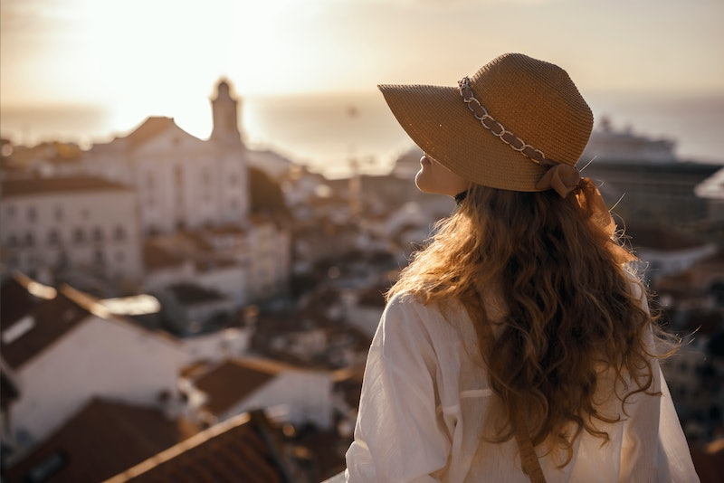 Blonde woman standing on the balcony and looking at coast view of the southern european city with se...