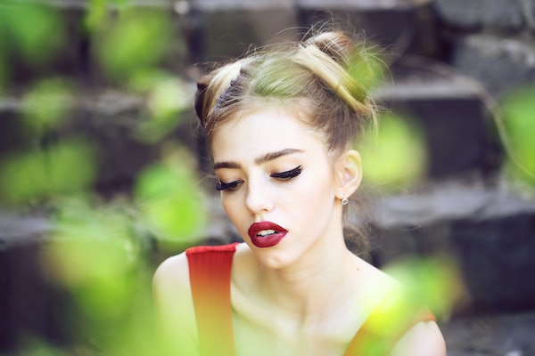Beautiful sad young woman on a stone stairs and green leaves background posing with red lips