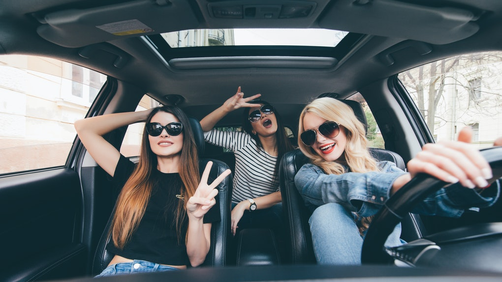 Group of friends having fun on the car. Singing and laughing in the city