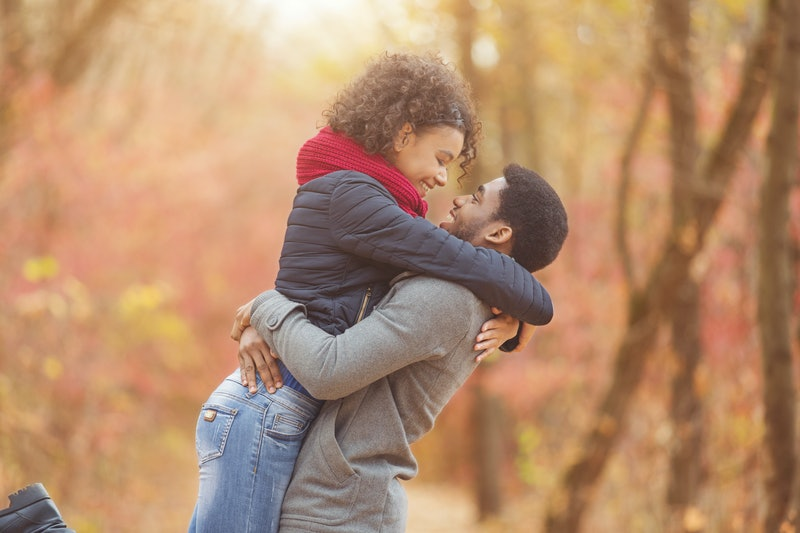 Happy couple in love enjoying autumn day, man holding girlfriend on hands, walking in park