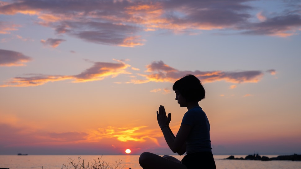 Sunset view of isolated woman meditating