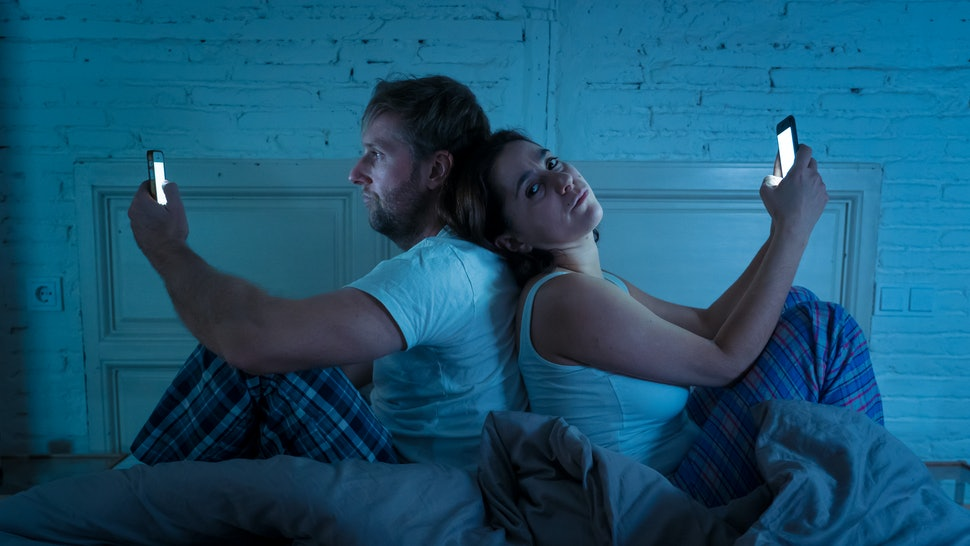 Sad man and woman married couple using their smart mobile phone in bed at night ignoring each other as strangers in relationship and communication problems and internet social network addiction.