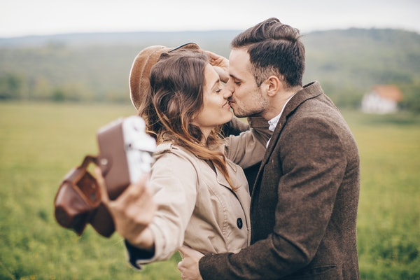 A happy couple kisses and hugs while taking a selfie with a camera in the countryside.