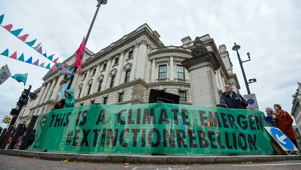 A banner erected by climate activists at a makeshift camp in Horse Guards Road outside HM Treasury, on day two of Extinction Rebellion's protest which is planned to close-down Westminster and other areas in the capital for two weeks.
