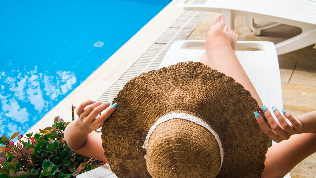 Girl sunbathes on a lounger by the pool