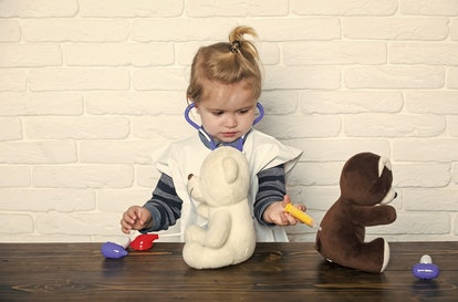 Boy doctor make injection to teddy bears with syringe. Child veterinarian cure toy animals with vaccine. Future profession concept. Vaccination, health, healthcare. Game, development, imagination.