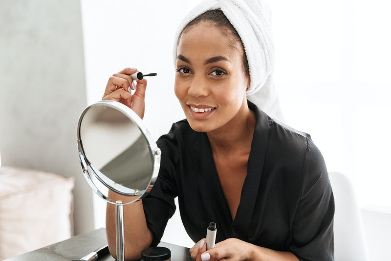Portrait of attractive african american woman in housecoat wrapped in white towel applying mascara against mirror at home