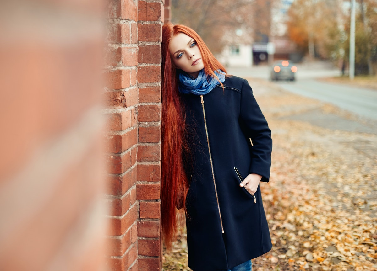 Woman with long red hair walks in autumn on the street. Mysterious dreamy look and the image of the girl. Redhead woman walking in the autumn the city. Cold cloudy autumn in the city