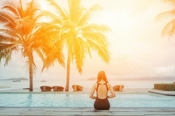 Amazing scenic rear view of sexy young woman with beautiful sun light relaxing on the pool of luxury hotel against summer holidays vacation, tropical beach on the island