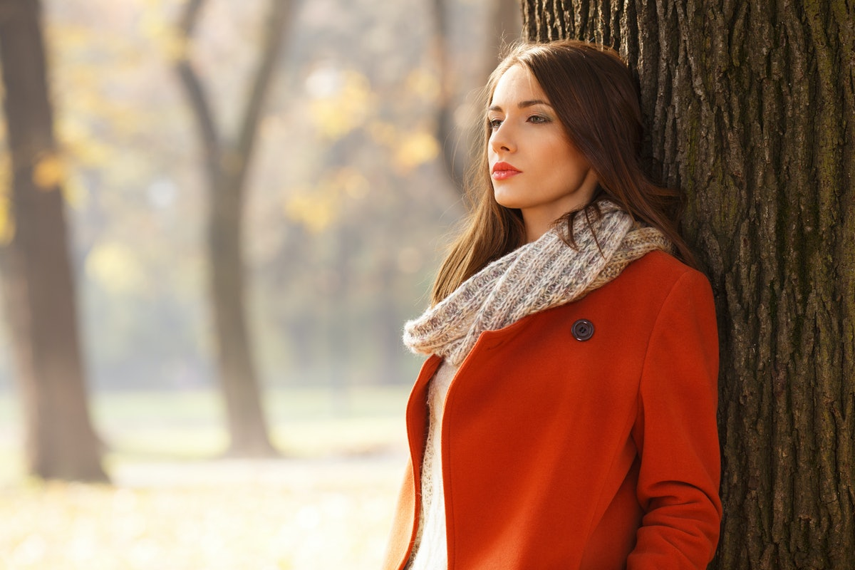 Portrait of a beautiful brunette woman in autumn park. She is looking into the distance.