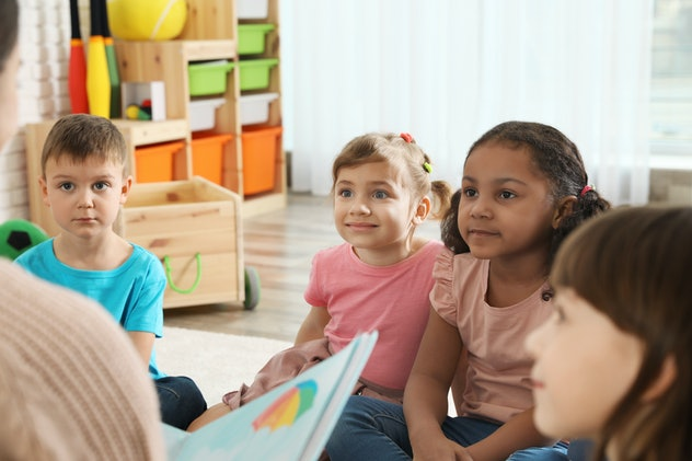 Kindergarten teacher reading book to cute little children indoors