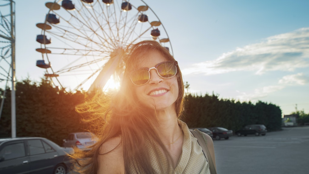 woman smiling cheerfully in front of a ferris wheel