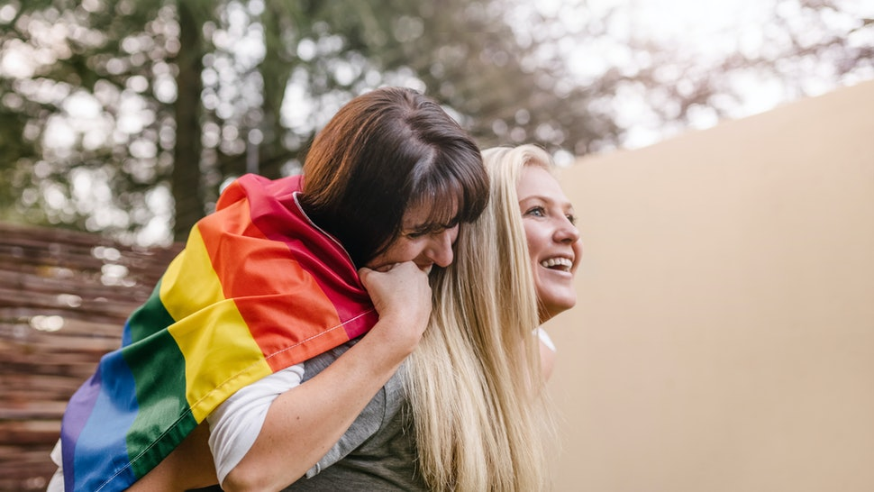 Happy proud lesbian couple having fun outdoors with gay flag