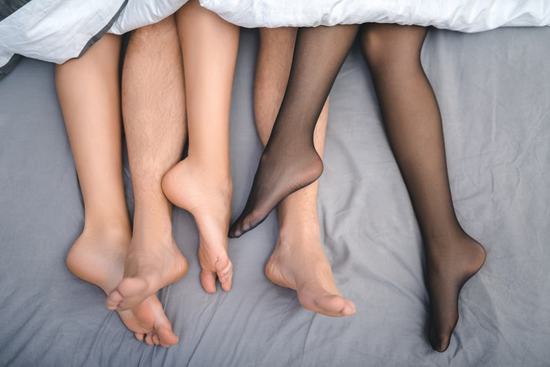 Close up feet of trio making love in bedroom. Sex party concept.