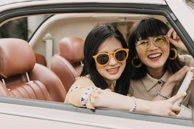 Happy friends driving vintage car