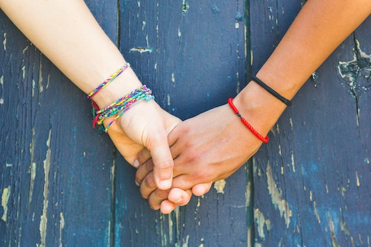 Two women holding hands with a wooden background. One is caucasian, the other is black. Multicultura...
