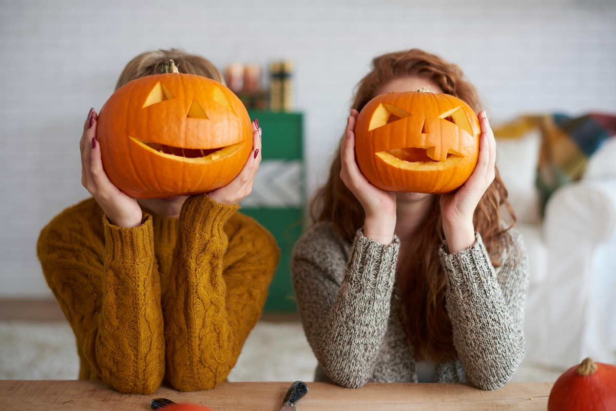 Two women wearing sweaters and holding pumpkins in front of their faces is a cute picture idea for I...