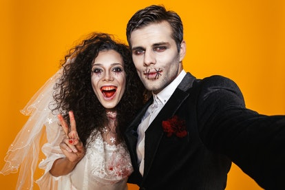Funny pretty zombie bride and groom in halloween costumes making selfie at camera and smiling isolat...