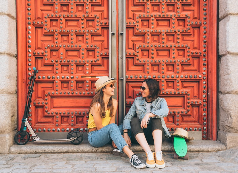 Young women lesbian couple looking and smiling each other in a red door background. Same sex happiness and joyful concept.