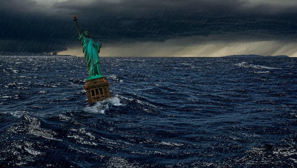 Surreal apocalyptic scene with The Statue of Liberty sinks in the ocean in the sunset under the dramatic cloudy sky and rain. Apocalypse of USA, America and the end of civilization concept