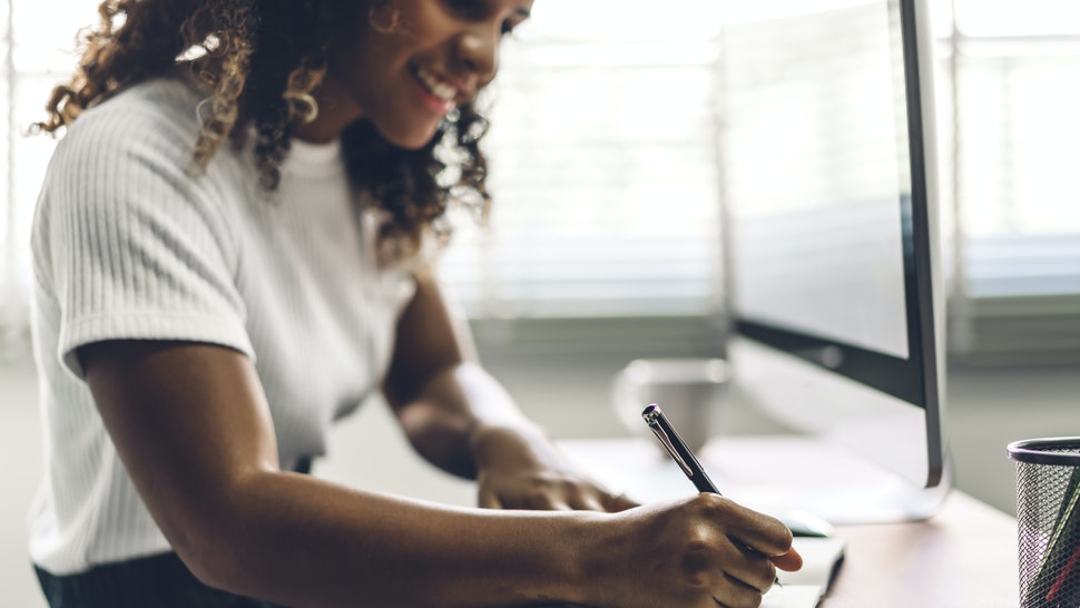 A Black woman sits at her desk. Workplace burnout can be reduced by talking about your mental health at work