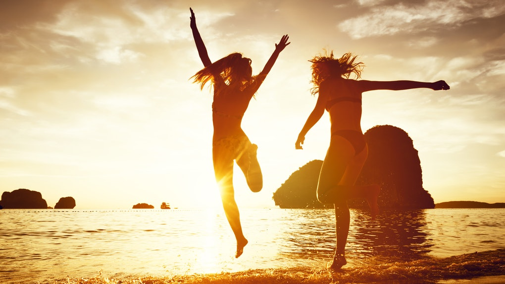 Two happy girls are jumping to sunset sea. Phranang beach, Krabi province, Thailand