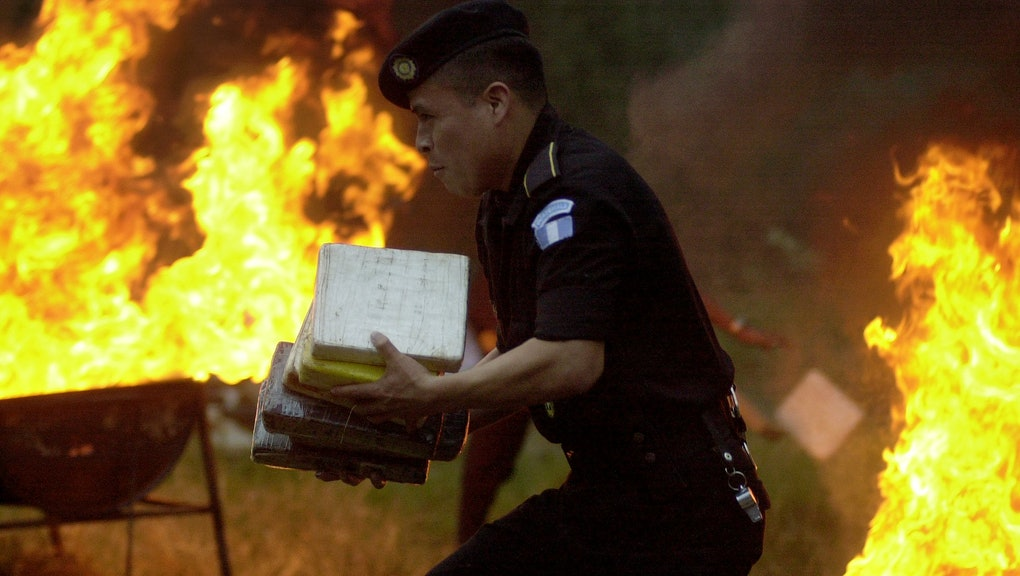 A police officer carries cocaine packages to have them burned at a police station in Guatemala City, . The police burned over 2 thousand pounds