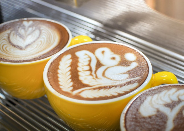 Cup of latte or cappuccino with latte art. Latte art coffee created by pouring steamed milk.