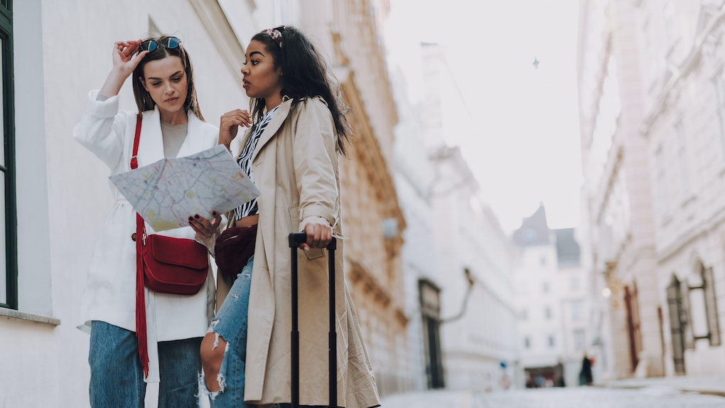 Attractive afro american lady with travel trolley bag looking at friend while she holding city map. Copy space in right side