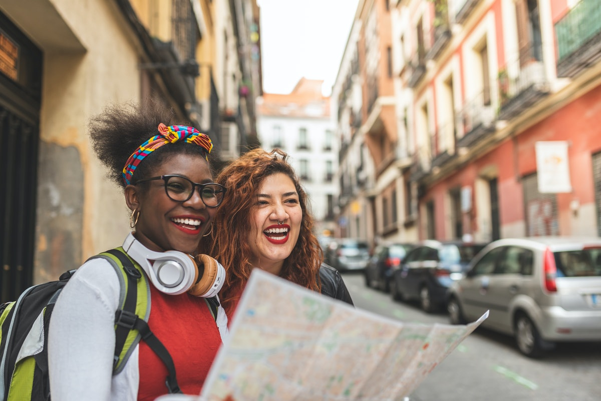 Two Afro American Girls Traveling Together. Two Friend Girls Using a Map in Europe. Latin American Girls on Holidays.Travel Concept.