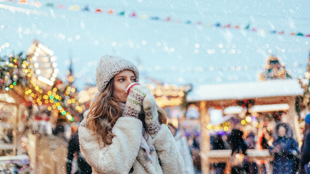 A woman dressed in a cap, fluffy coat, and gloves drinks hot chocolate at snowy holiday market.