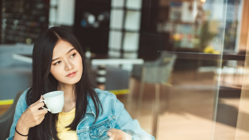 Asian woman with beautiful smile hold mobile phone during rest in coffee shop.Attractive woman drinking coffee.Reflection glass window.