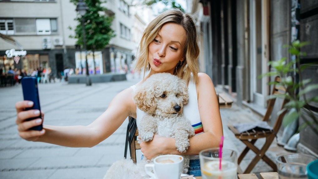A blonde woman takes a picture with her dog while eating at a dog-friendly brunch spot in NYC.
