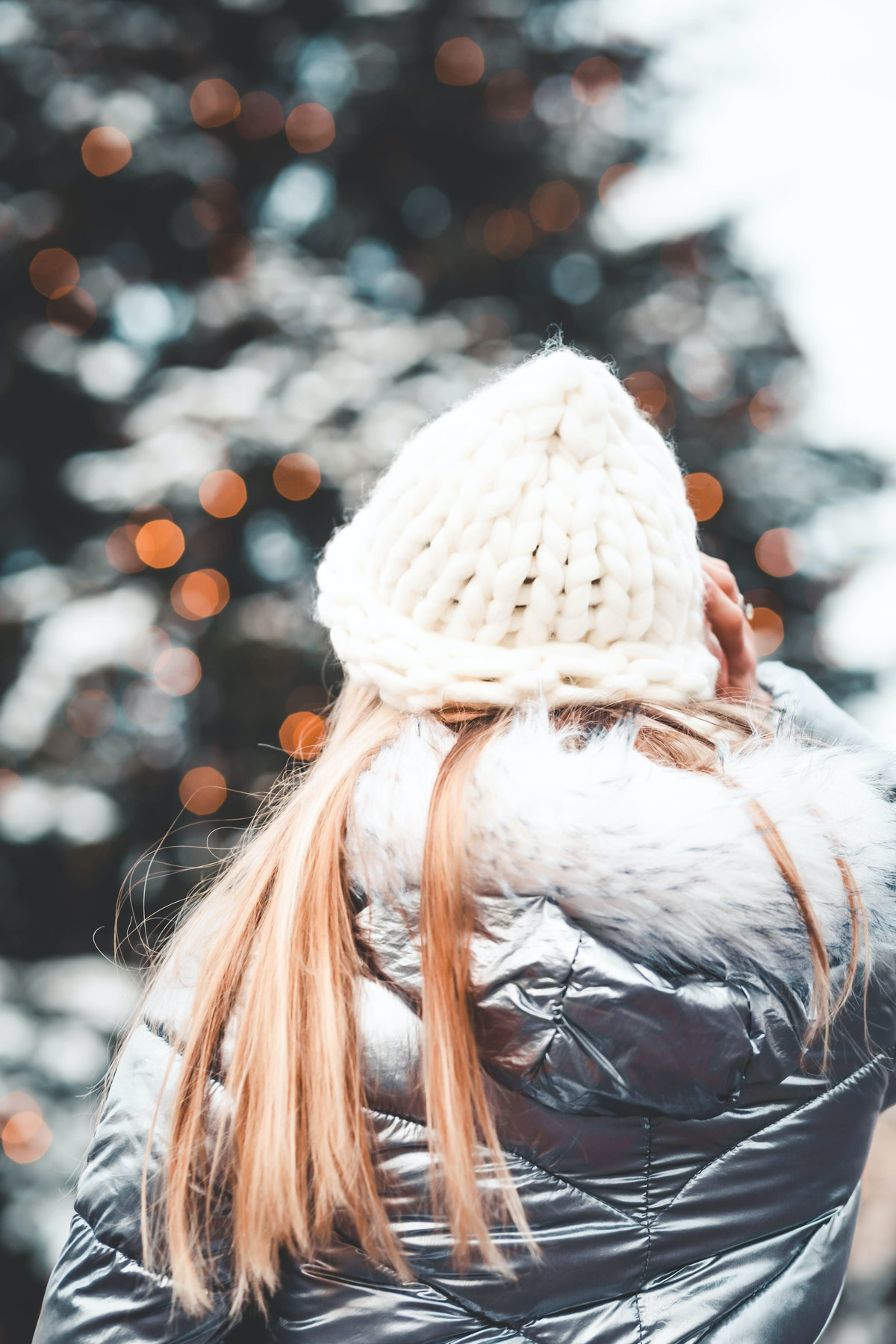 A blonde woman faces a holiday tree at the market in a metallic coat and knit hat.
