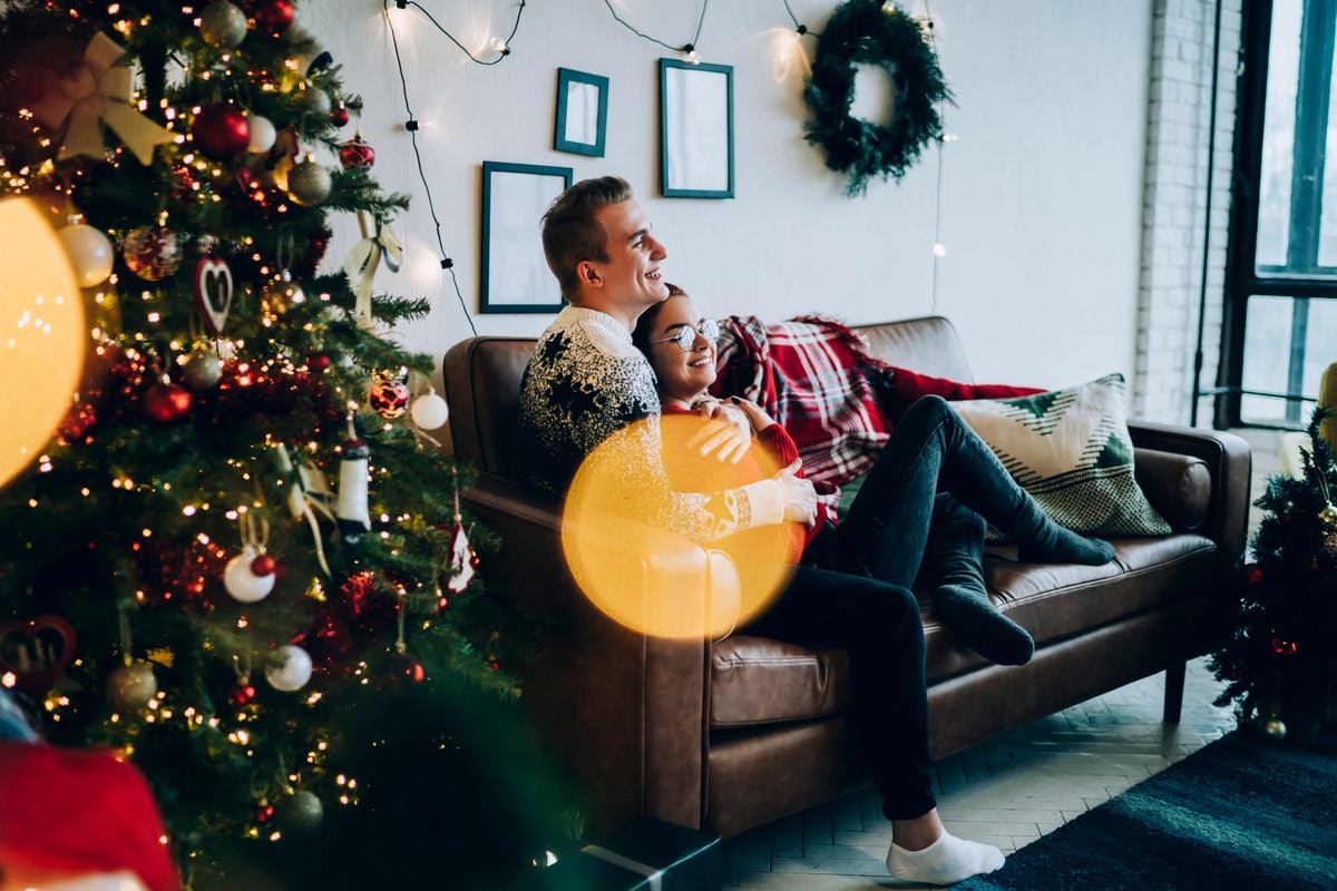 A guy in a festive sweater cuddles with his girlfriend on the couch, watching a romantic holiday movie near a Christmas tree.