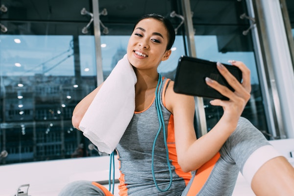 close up view of smiling asian sportswoman  wiping neck and taking selfie at gym