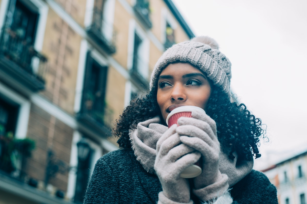 A woman in the city holds a cup of hot chocolate and wears chic winter clothes.