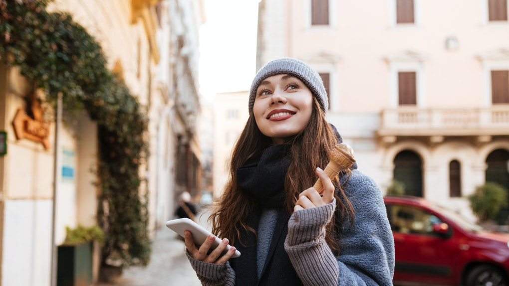 Cheerful cute young woman using cell phone and eating ice cream in the city