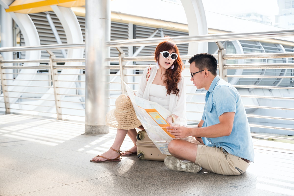 Lost and Confused Couple sitting on the floor and luggage to discussing find the best way on the Map Together.