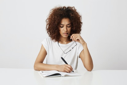 African girl thinking writing in notebook sitting at table over white background. Copy space.