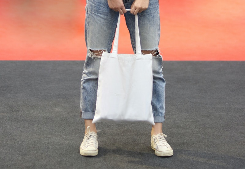 model hold blank white fabric tote bag for saving the environment on street fashion