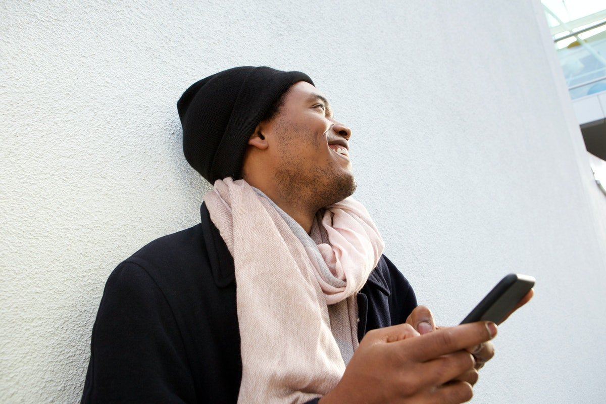 Close up portrait of handsome young african american man laughing with cellphone by white background...