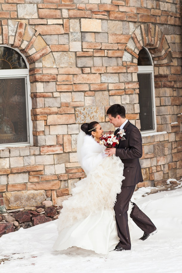 A happy, newly married couple laughs in the snow next to a brick wall on their wedding day.