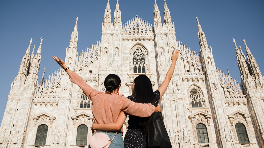 Two stylish best friends pose in front of the Duomo in Milan, Italy, during a holiday trip.