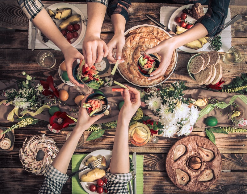 Traditional Easter celebration, Easter holiday party. Holiday friends or family at the festive table with rabbit meat, vegetables, pies, eggs, top view. Friends hands eating and drinking together.