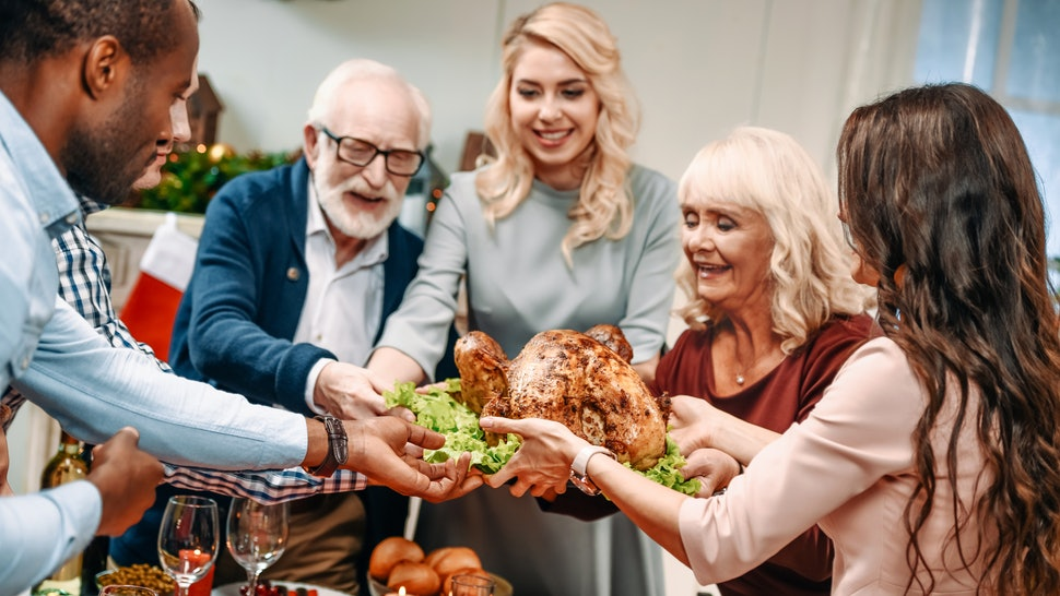 beautiful large family holding christmas turkey for holiday dinner