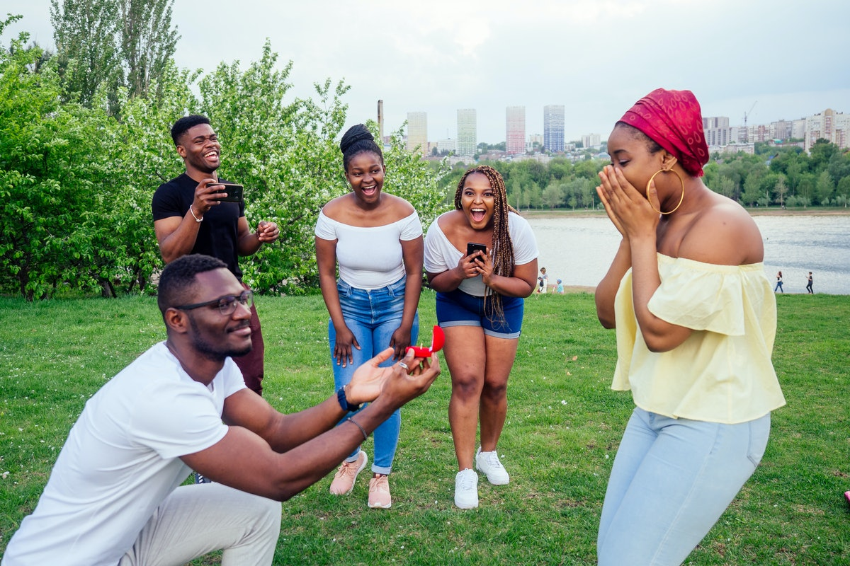american male standing on one knee asking woman marriage giving ring proposing surprised shocked whi...